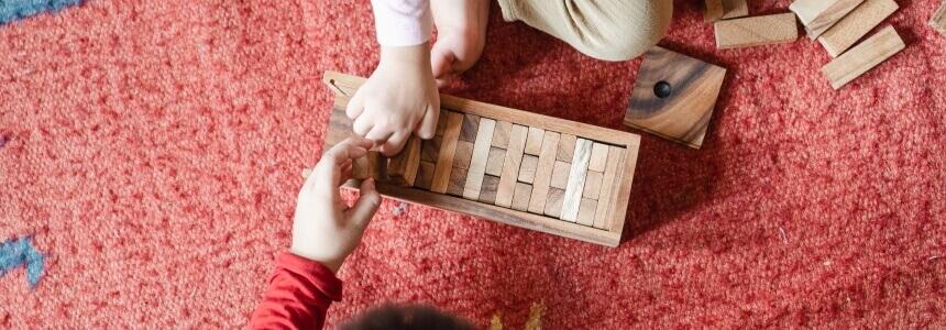 Kinderhände, die mit Holzspielzeug spielen. Vielleicht sind sie beim Kinderarzt zu den U-Untersuchungen.