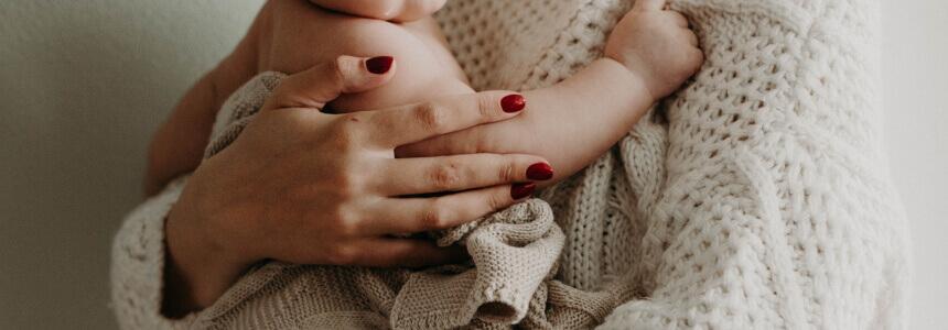 Baby auf dem Arm der Mama. Häufig werden Babys beim Wachstumsschub getragen.des