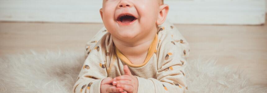 Baby, das auf dem Bauch liegt und lacht. Ein Zähnchen ist zu sehen.