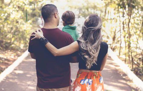 Familienleben im Wald. Mama, Papa und Kind stehen auf Waldlichtung.