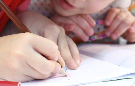 Vorschulkinder die gerade etwas schreiben oder nachmalen.