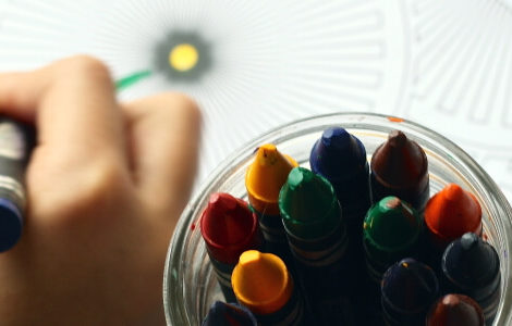 Kind malt mit Wachsstiften ein Bild. Das spielen und kreativ sein ist wichtig für die Kinder.