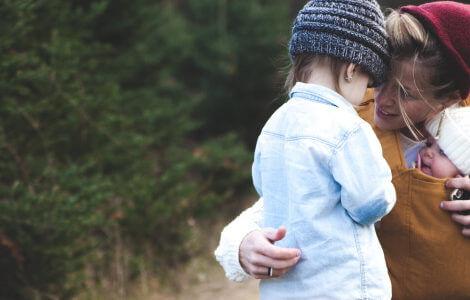 Mama mit Baby in der Trage, das ihre große Tochter in den Arm nimmt und so ihre Liebe zeigt.