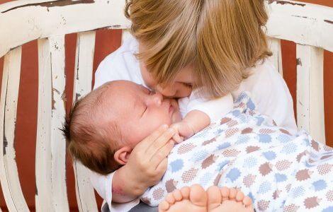 Geschwister, die auf einer Bank sitzen. Der große Bruder gibt dem Baby einen Kuss.