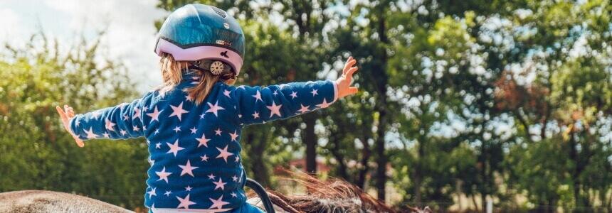 Ein selbstbewusstes Kind, das lernt auf einem Pferd zu reiten.